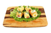 Uovo rotoli con crema di formaggio e paprika, su tavola di legno, isolato su bianco — Foto Stock