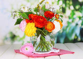 Excellent buttercup flowers in glass vase on wooden table on natural background — Stock Photo