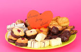 Sweet cookies on plate with valentine card on pink background — Stock Photo