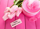 Beautiful bouquet of tulips and gift for Mother's Day on pink wooden background — Photo