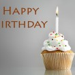 Tasty birthday cupcake with candle, on grey background — Stock Photo