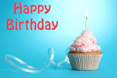 Tasty birthday cupcake with candle, on blue background — Stockfoto