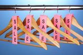 Wooden clothes hangers as sale symbol on blue backgroun — Stock Photo