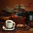Cup of coffee, grinder, turk and coffee beans on brown background — Stok fotoğraf