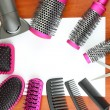 Постер, плакат: Comb brushes hairdryer and cutting shears on wooden background