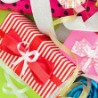 Stock Photo: Rolls of Christmas wrapping paper with ribbons, bows on color background