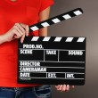 Stock Photo: Movie production clapper board in hands on grey background