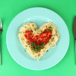 Cooked spaghetti carefully arranged in  heart shape and topped with tomato sauce, on color background — Stockfoto