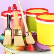 Set for painting: paint pots, brushes, palette of colors on lilac background — Stock Photo #23111662