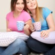 Two girl friends smiling on room — Stock Photo