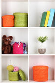 Color wicker boxes on cabinet shelves — Stockfoto