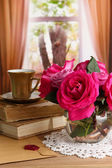 Beautiful pink roses in vase on wooden table on window background — Stock Photo