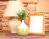 Ramki kolorowe zdjęcie, lampa i kwiaty na drewnianym stole na tle kamiennego muru — Zdjęcie stockowe