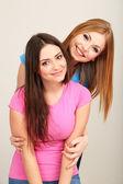 Twee vriendinnen knuffelen op grijze achtergrond — Stockfoto