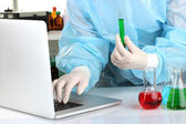 Scientist entering data on laptop computer with test tube close up — Stock Photo