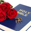 Wedding rings with roses on bible isolated on white — Stock Photo #23128702