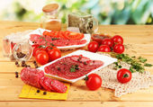 Tasty salami on plates on wooden table on natural background — Stock Photo