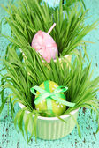 Easter eggs in bowls with grass on green wooden table close up — Stock Photo