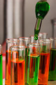 Laboratory pipette with drop of color liquid over glass test tubes, close up — Foto de Stock