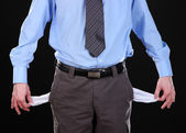 Business man showing his empty pockets, on black background — Stock Photo