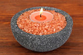Candle in stone bowl with marine salt, on wooden background — Stock Photo