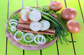 Composition with herbs and onions on wooden table — Stock Photo