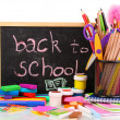 The words 'Back to School' written in chalk on the small school desk with various school supplies close-up isolated on white — Stock Photo #23186956