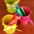 Colorful pencils and felt-tip pens in color pails close-up on wooden table — Stock Photo #23187074