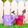 Stock Photo: Gardening tools on green grass on wooden fence background