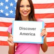 Young woman young woman holding tablet on background of American flag — Stock Photo #23187660