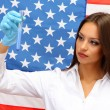 Portrait of female doctor or scientist showing and analyzing liquid in flask over American Flag background — Stock Photo