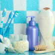 Bath accessories on shelf in bathroom on blue tile wall background - Stock Photo