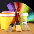 Paint pots, paintbrushes and coloured swatches on wooden table on dark yellow background — Стоковая фотография