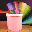 Paint pot, paintbrush and coloured swatches on wooden table on dark purple background — Stock Photo #23188356