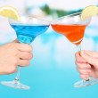 Cocktails in men's and women's hands on pool background — Foto de Stock