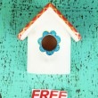 Decorative nesting box and sign on color background - Stockfoto