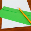 Envelope with pencil and paper on wooden background — Stock Photo