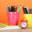 Colorful pencils in two pails with copybooks on table on orange background — Stock Photo #23188806