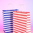 Stripped bags on light pink background — Stock Photo #23188988