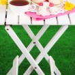 Beautiful composition with cup of tea and marshmallow on wooden picnic table on natural background — Stock Photo #23189678