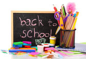 The words 'Back to School' written in chalk on the small school desk with various school supplies close-up isolated on white — Stock Photo