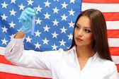 Retrato de mujer médico o científico de muestra y análisis de líquido en el frasco sobre fondo de bandera americana — Foto de Stock