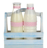 Milk in bottles in wooden box isolated on white — Stock Photo