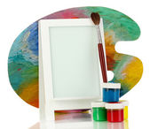 Photo frame as easel with artist's tools isolated on white — Stock Photo