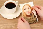 Zdjęcie w ręce i filiżankę kawy na drewnianym stole — Zdjęcie stockowe