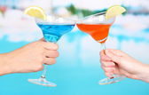 Cocktails in men's and women's hands on pool background — Stock Photo