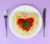 Cooked spaghetti carefully arranged in heart shape and topped with tomato sauce, on color background — Stock Photo