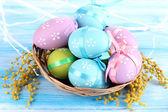 пасхальные яйца в корзину и mimosa цветы на синем фоне деревянные — Стоковое фото