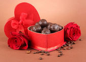 Chocolate candies in gift box, on brown background — Stock Photo