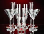 Cocktail und wein gläser auf dunkelroten hintergrund — Stockfoto